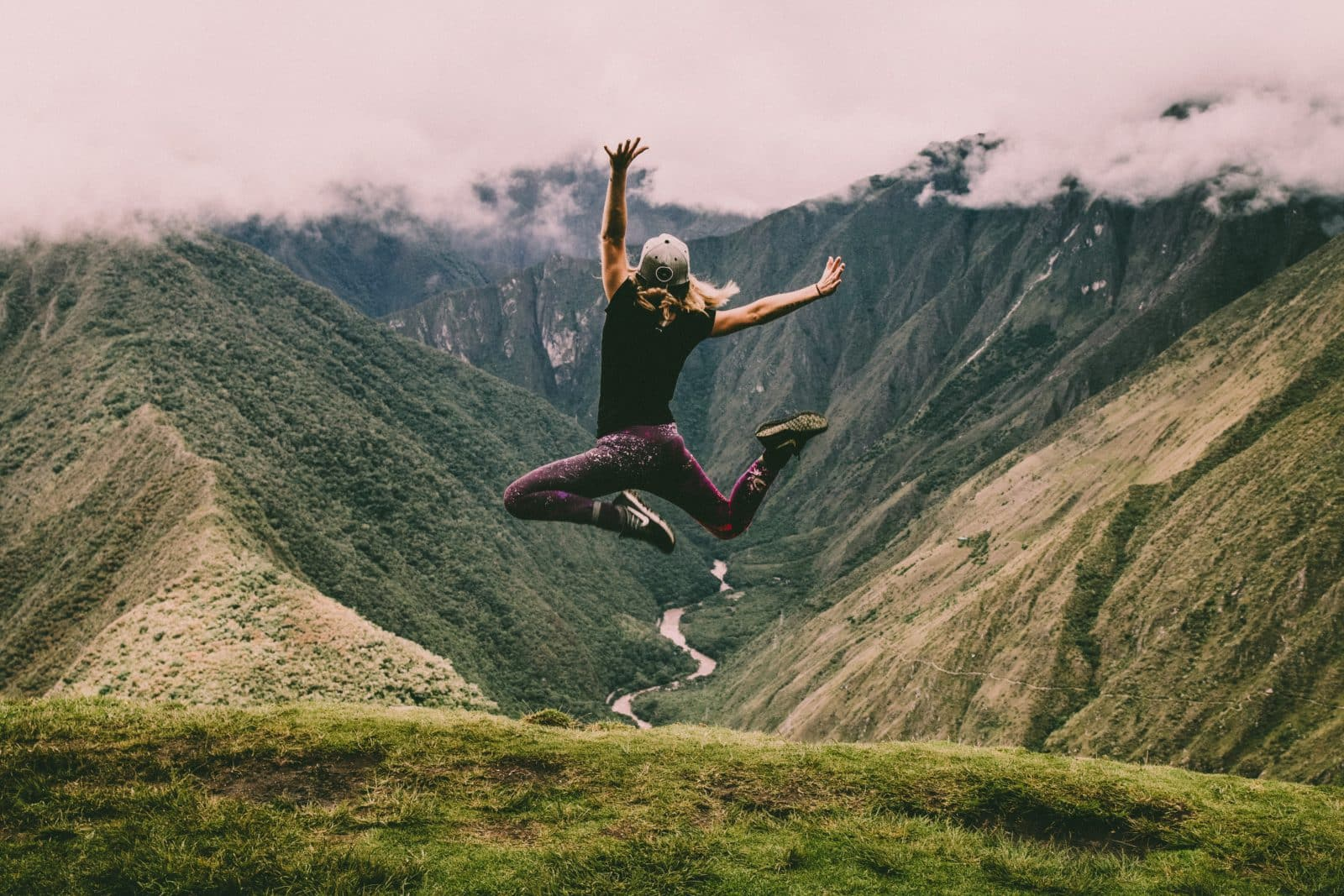 A traveller jumps in the air overlooking a scenic landscape