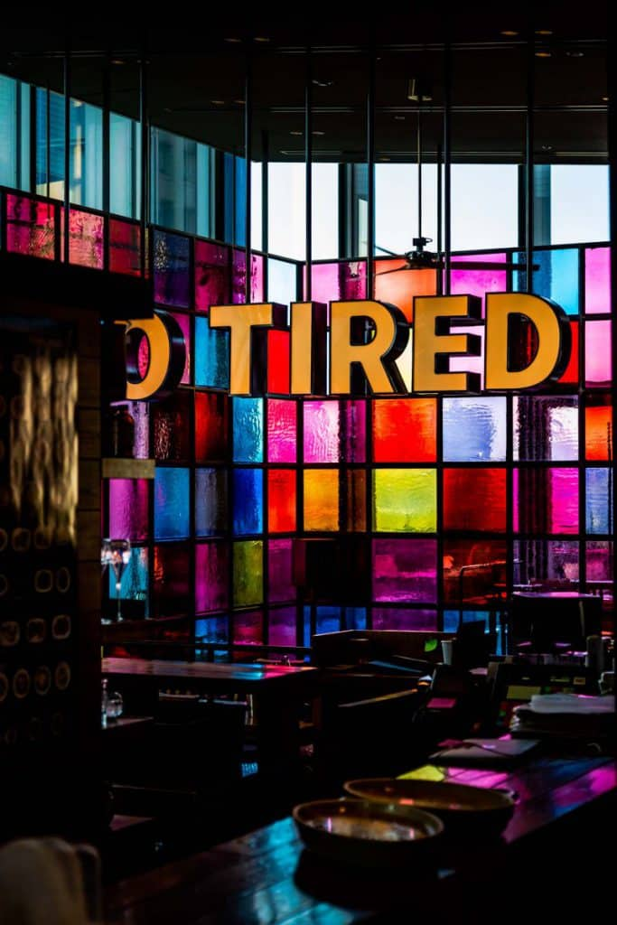 A sign saying 'Tired' in front of coloured windows