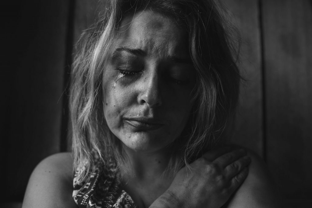A black-and-white photo of a woman crying