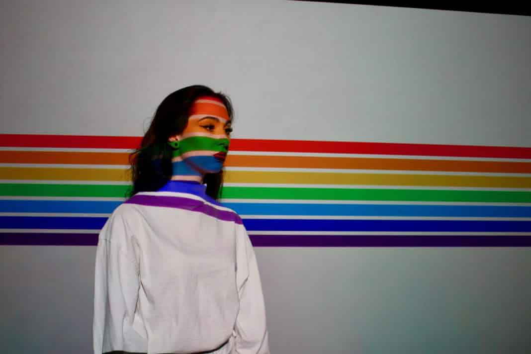 A woman stands in front of the LGBT flag.