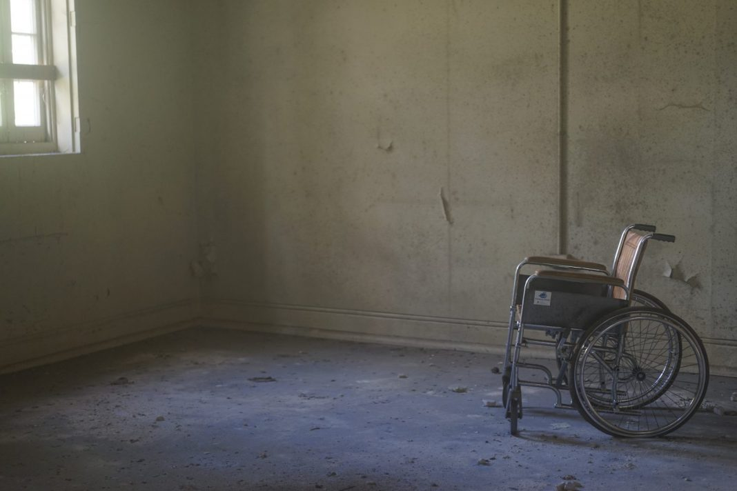 An empty wheelchair in a tatty room