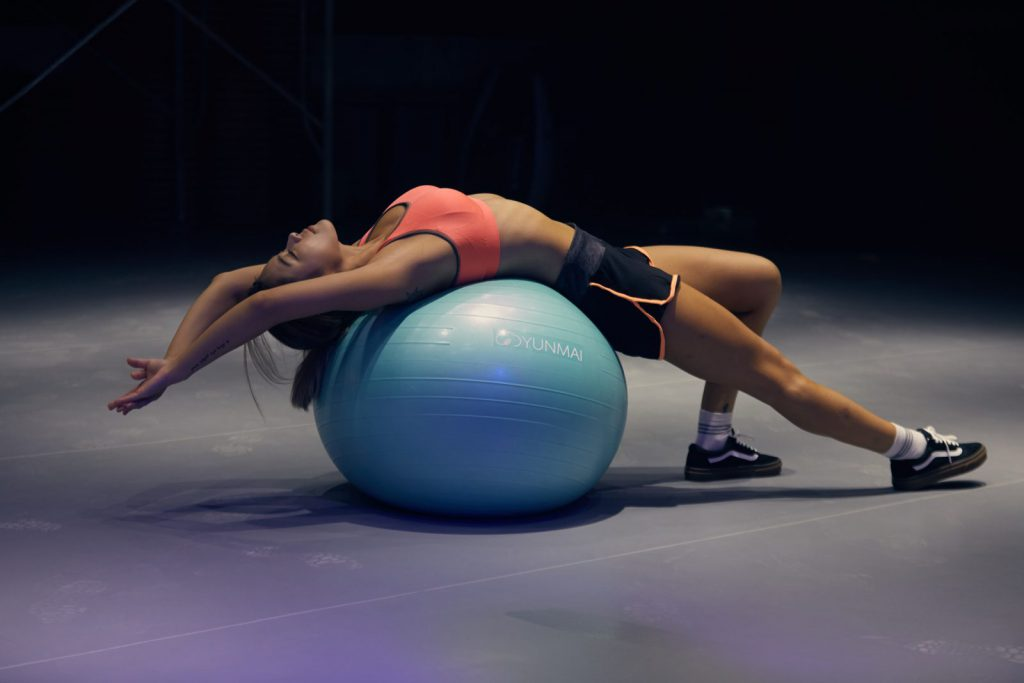 A young woman stretches using an exercise ball