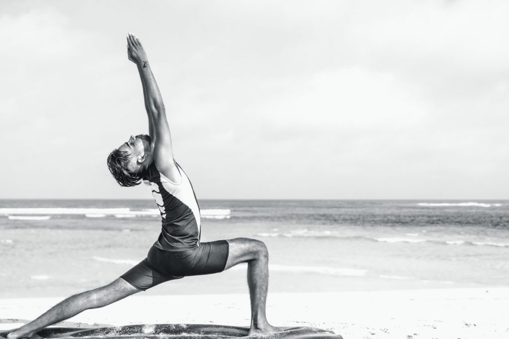 A man does yoga on the beach