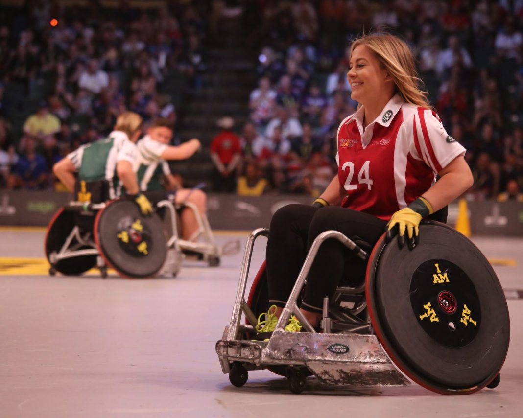 A smiling young woman in a wheelchair plays wheelchair basketball