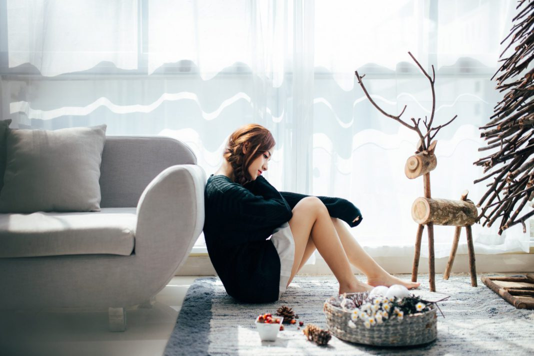 A young woman looks sad, sitting on a floor surrounded by Christmas decorations