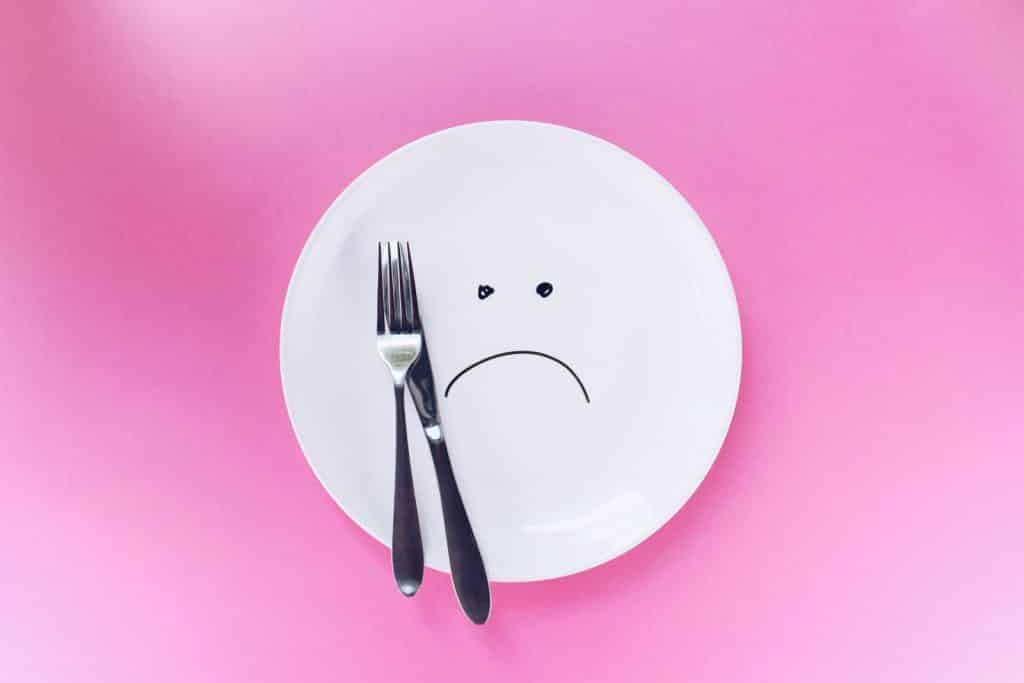 An empty plate with a sad face