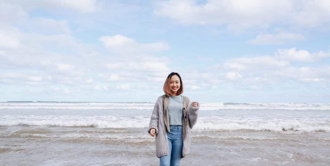 A woman stands smiling on Goolwa beach