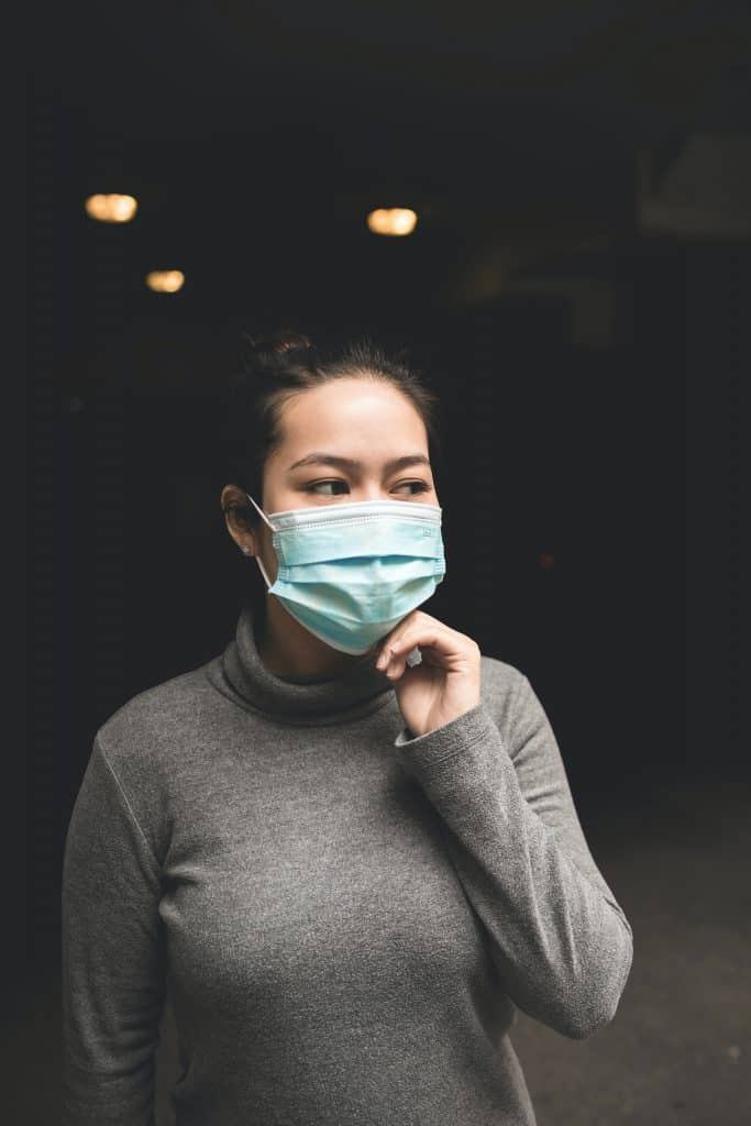 woman wearing teal mask and gray turtle-neck shirt
